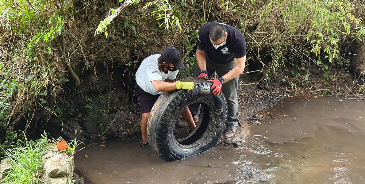 Voluntários retirando pneu do rio