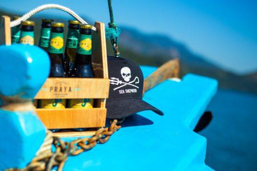 Garrafas de cerveja Praya junto a um boné do Sea Shepherd