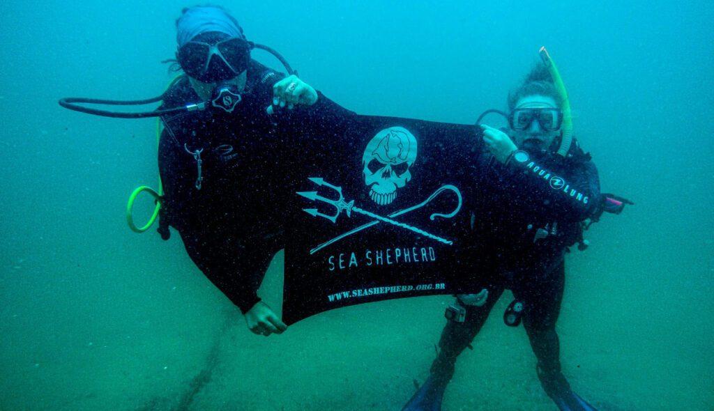 Mergulhadores segurando bandeira da Sea Shepherd