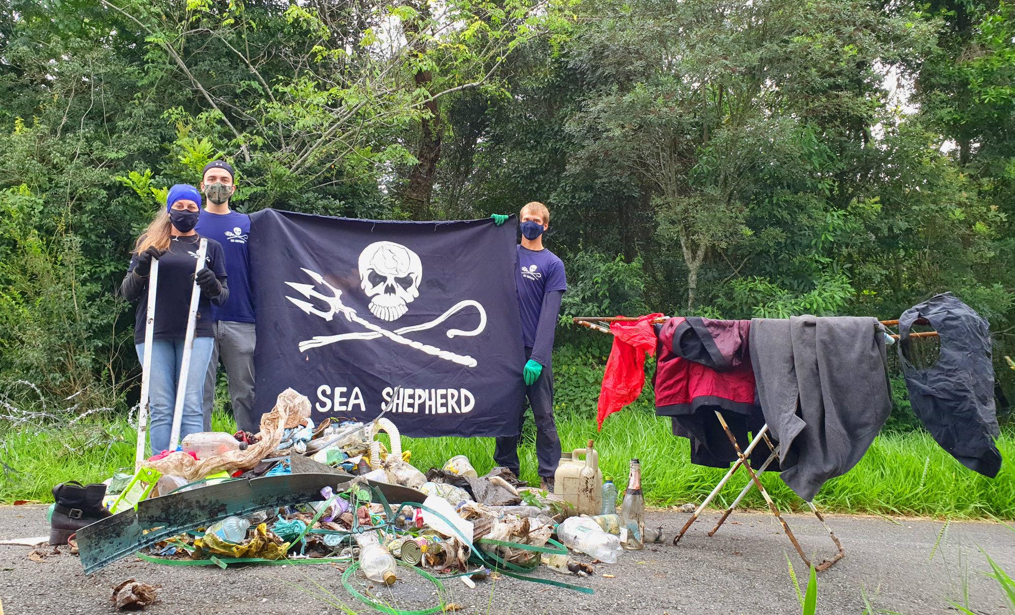 Voluntários na frente de pilha de lixo segurando bandeira da Sea Shepherd