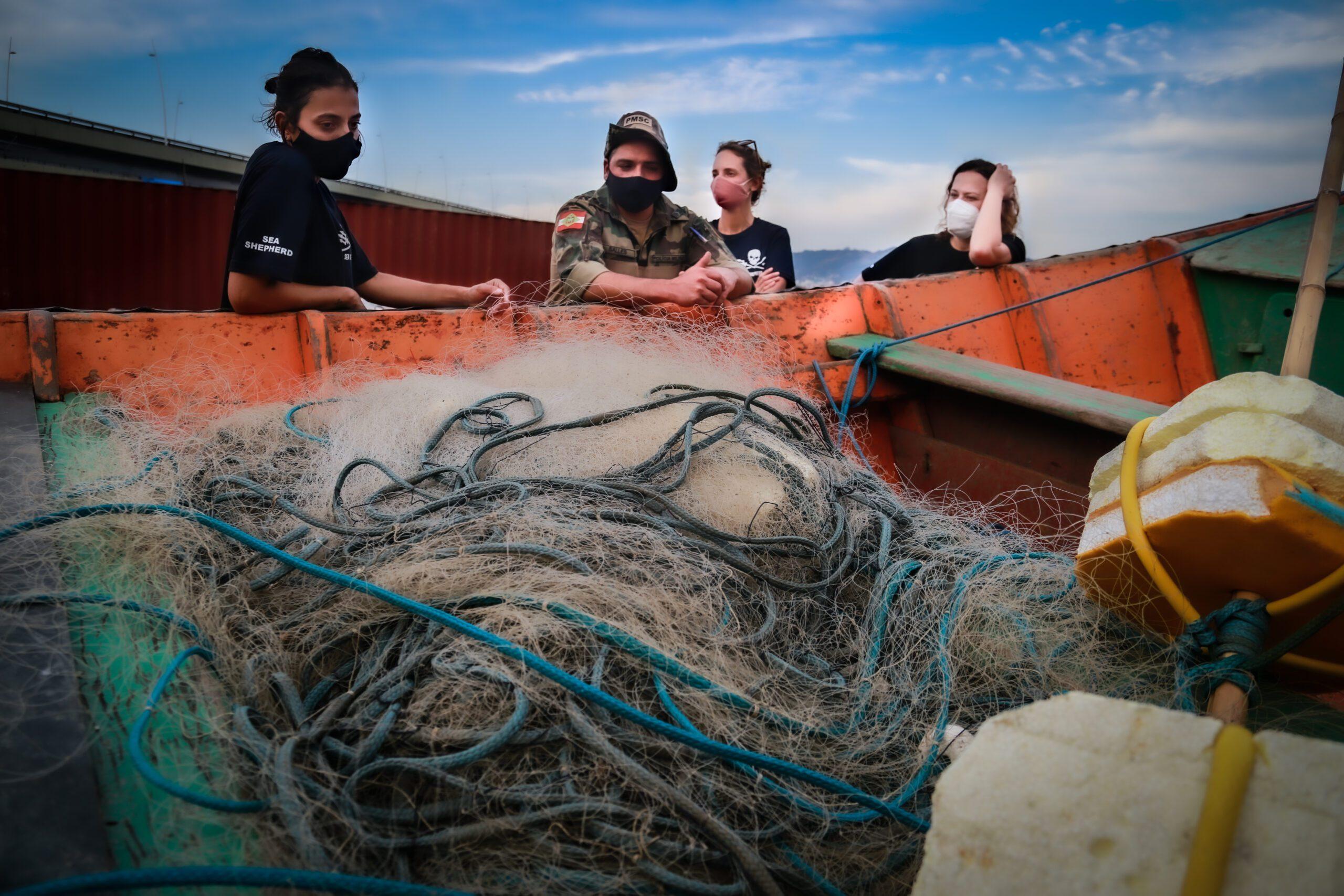 Voluntários da Sea Shepherd e cabo da Polícia Militar Ambiental observam rede apreendida