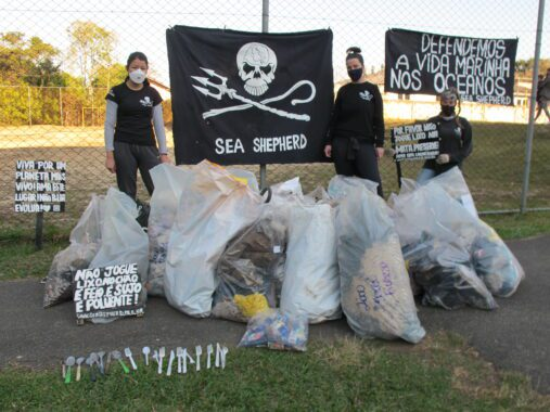 Voluntárias com lixo recolhido e placas de conscientização