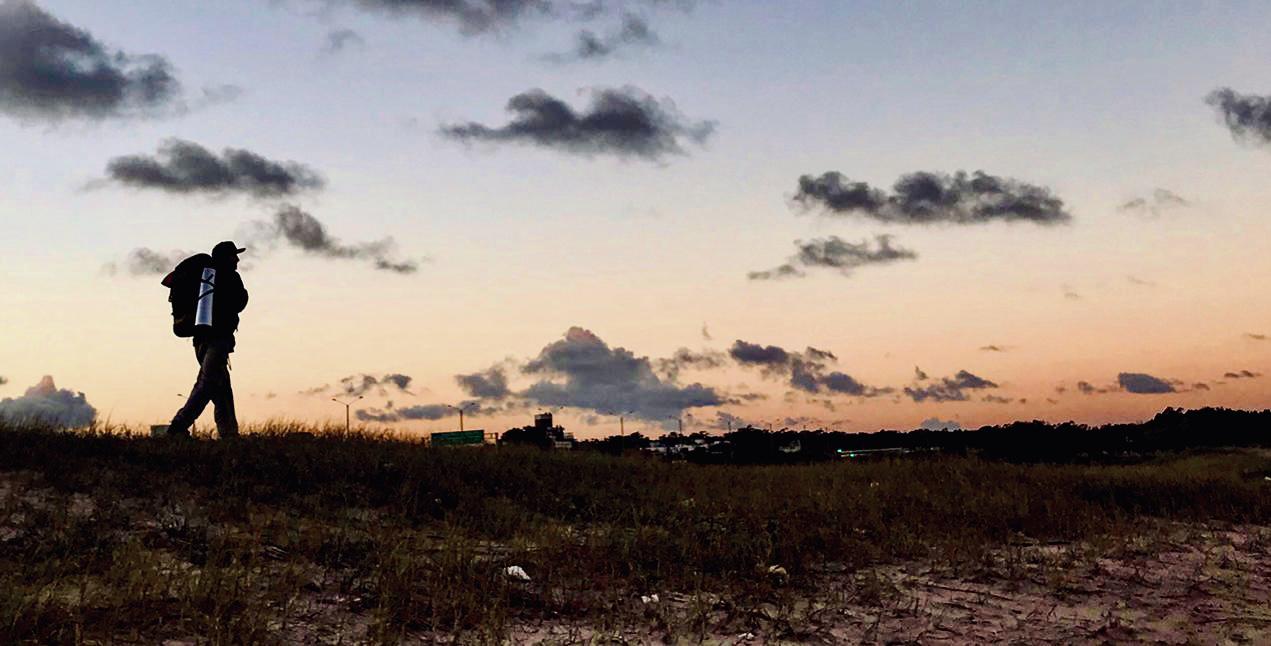 Plácido Salles andando em praia com horizonte ao fundo