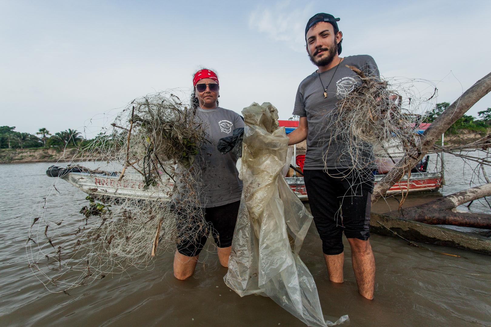Tripulação segura redes de pesca retiradas do rio